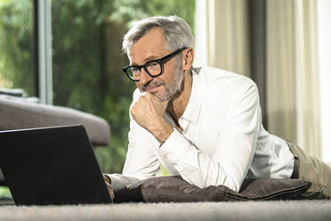 Smiling senior man with grey hair in modern design living room working on laptop - SBOF02121