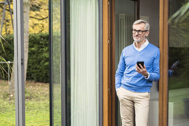 Senior man with grey hair standing in front of his modern design home holding smartphone - SBOF02124