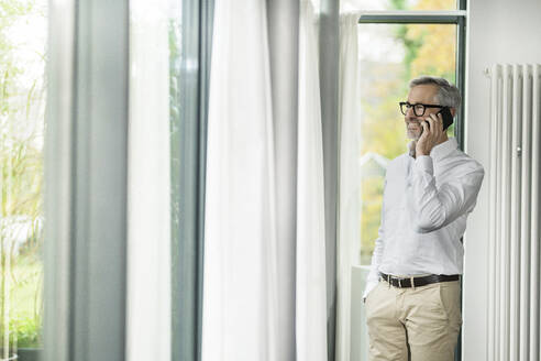 Smiling senior man with grey hair talking on the phone in modern design home with large windows - SBOF02139