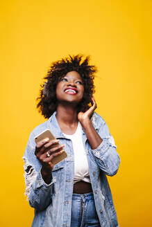 Portrait of a happy young woman in studio with smartphone and headphones - DGOF00478