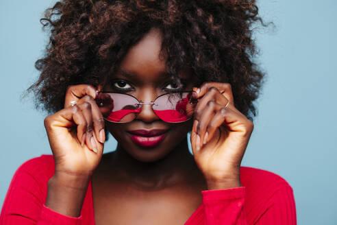 Portrait of beautiful young woman wearing sunglasses in studio - DGOF00484