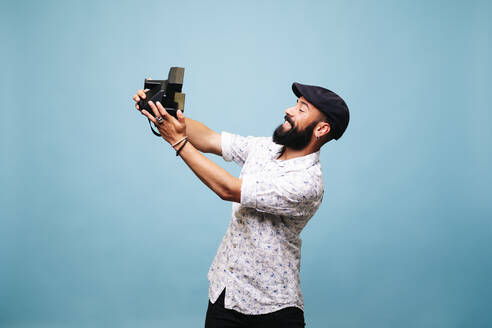 Bearded young man in studio taking selfie with instant camera - DGOF00487