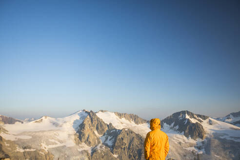 Hiker looking at view of glaciated mountains in Canada. - CAVF75534