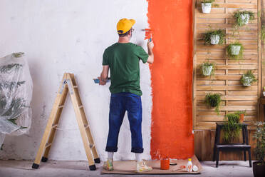 Rear view of man painting orange wall in his garden terrace - RTBF01424