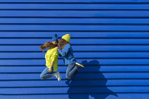 Two teenage girl wearing matching clothes jumping in the air in front of blue background - ERRF02679