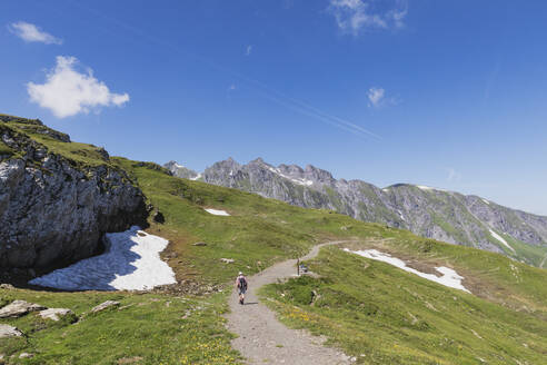 Switzerland, St Gallen Canton, Glarus Alps, Man hiking the Panoramic hiking trail in the Tectonic Arena Sardona - GWF06478