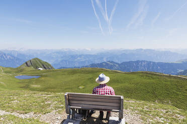 Switzerland, St Gallen Canton, Man resting on bench, looking on the mountains - GWF06487