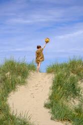 Teenage girl with hat standing in dunes at the beach, Farhult, Skane, Sweden - LBF02890