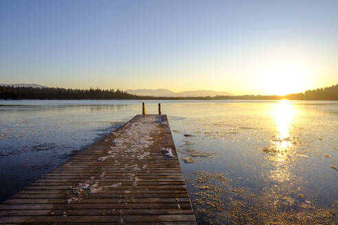 View of frozen Kirchsee with jetty at sunset, Bavaria, Germany - LBF02902