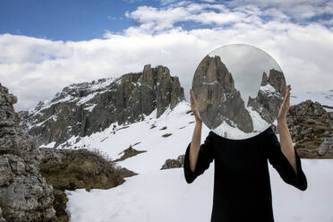 Woman covering head with mirror, reflecting Sella group in winter, Dolomites, Alto Adige, Italy - PSTF00587