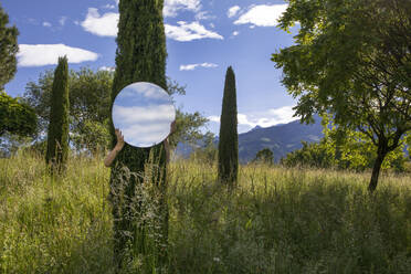 Woman hiding behing tree, holding mirror, reflecting the sky - PSTF00596