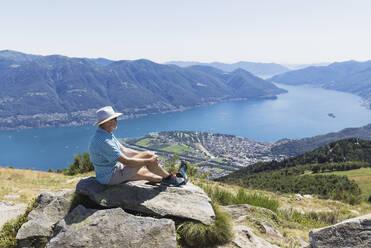 Hiker at Cimetta mountain top looking towards Lago Maggiore and Ascona, Locarno, Ticino, Switzerland - GWF06497