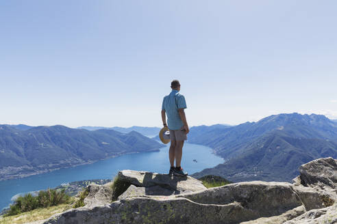 Hiker at Cimetta mountain top looking towards Lago Maggiore and Ascona, Locarno, Ticino, Switzerland - GWF06500