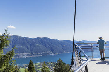 Hiker standing on viewing platform Cardada above Locarno looking towards Lago Maggiore, Ticino, Switzerland - GWF06503