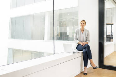 Blond businesswoman with laptop, sitting on windowsill in office building - PESF01847