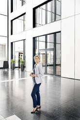 Successful businesswoman standing in entrance hall of office building - PESF01862