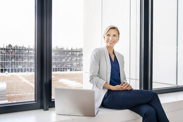 Blond businesswoman with laptop, sitting on windowsill in office building - PESF01865