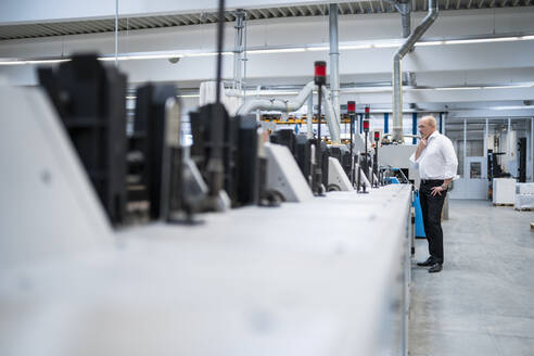 Businessman standing at a machine in a factory - DIGF09330