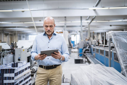 Businessman using tablet in a factory - DIGF09348