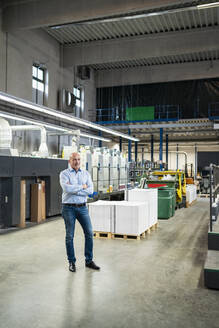 Confident businessman standing in a factory - DIGF09381