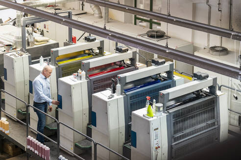 Businessman standing at machines in a printing plant - DIGF09390