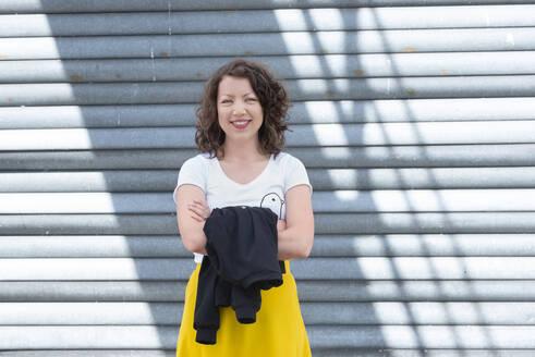 Portrait of smiling brunette woman at roller shutter - HBIF00052