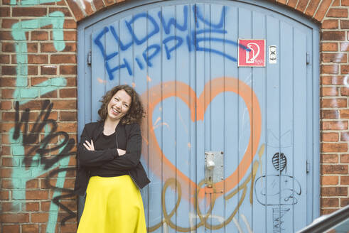 Portrait of a happy brunette woman standing in front of a brick wall with an old gate and graffiti - HBIF00061