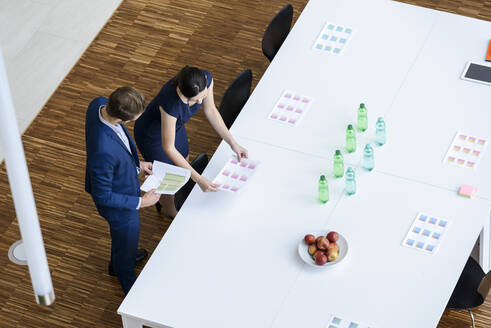 Businessman and woman preparing boardroom for a meeting, elevated view - BMOF00209