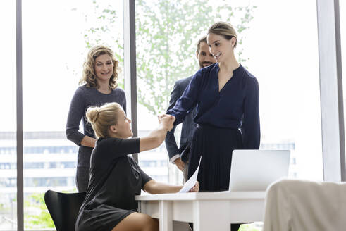 Businesswoman greeting colleagues in her team - BMOF00224
