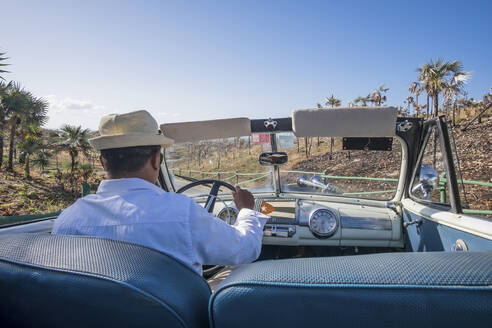 Taxi driver driving a vintage convertible car on Cuba - PAF01946