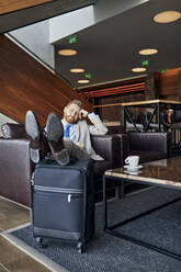 Businessman relaxing in hotel lobby - ZEDF03101