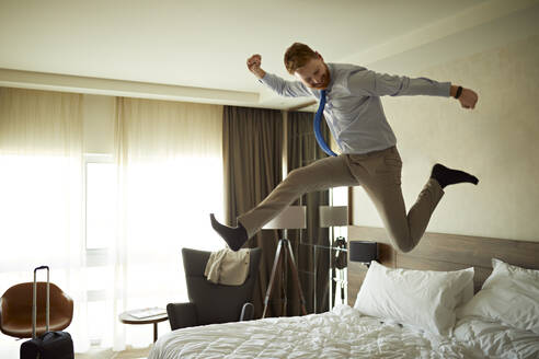 Excited businessman jumping on bed in hotel room - ZEDF03113