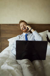 Businessman lying on bed in hotel room laughing on the phone - ZEDF03116