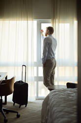 Businessman in hotel room looking out of window - ZEDF03131