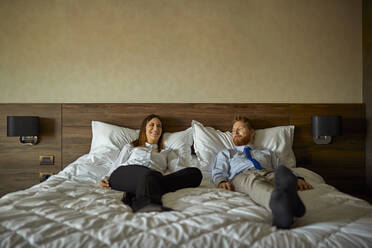 Businessman and businesswoman lying on bed in hotel room - ZEDF03149