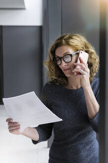 Businesswoman holding documents and calling at the office - BMOF00265