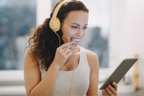 Woman with headphone, using digital tablet, smiling, eating vegetables - JOSEF00042