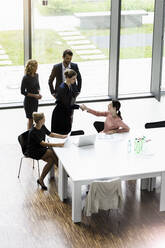 Business people shaking hands in modern office conference room - BMOF00284