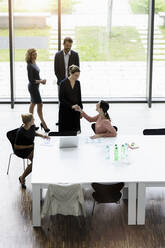 Business people shaking hands in modern office conference room - BMOF00287