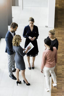 Business people standing in modern office building discussing project - BMOF00290