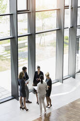 Business people standing in modern office building discussing project - BMOF00293