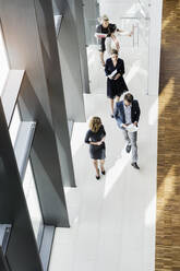 Business people walking in modern office building - BMOF00296