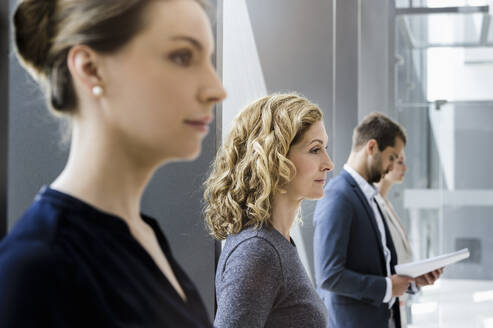 Businesswomen and businessmen waiting in line in the office - BMOF00299