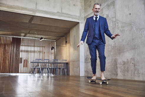 Senior businessman skateboarding in his office - MCF00613