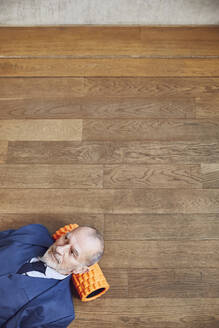 Senior businessman relaxing on wooden floor, resting on fascia roll - MCF00616