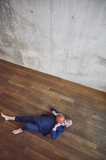 Senior businessman lying on wooden floor, playing with basketball - MCF00619
