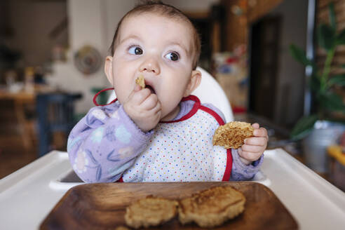 Portrait of baby girl sitting in high chair eating homemade oatmeal cookies with hands - GEMF03457