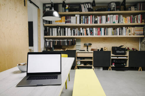 Laptop on table in loft office - GUSF03345