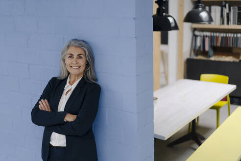 Portrait of smiling grey-haired businesswoman standing at a blue wall in a loft office - GUSF03351
