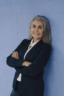 Portrait of smiling grey-haired businesswoman standing at a blue wall - GUSF03354